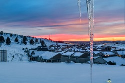 A colorful frigid winter sky and sunset over Spokane Washington seen from a hilltop home covered with snow with an icicle in the foreground.