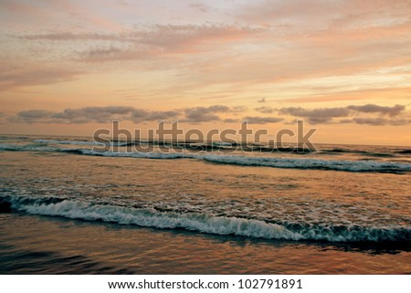 A colorful, glowing, painted looking sky and ocean at sunset