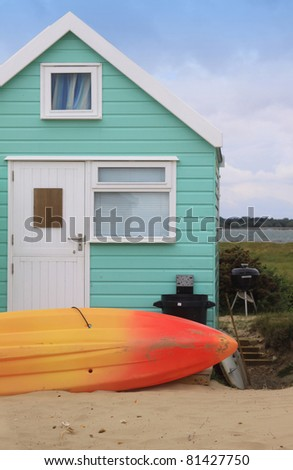 A colorful green wooden beech hut with an orange and yellow surf board resting in the sand to the front of the hut. Located in the South of England at Christchurch, Dorset, England. - stock photo