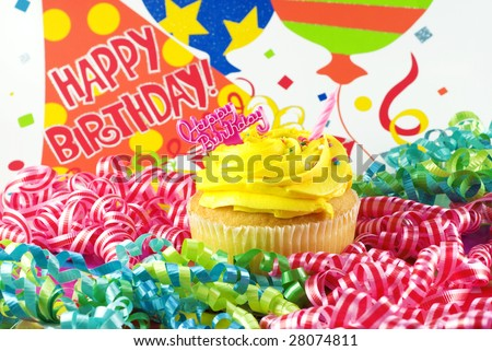 A colorful Happy Birthday Cupcake with one unlit candle with birthday decorations and Happy Birthday message
