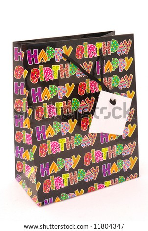 A colorful happy birthday gift bag with plain tag isolated on white background