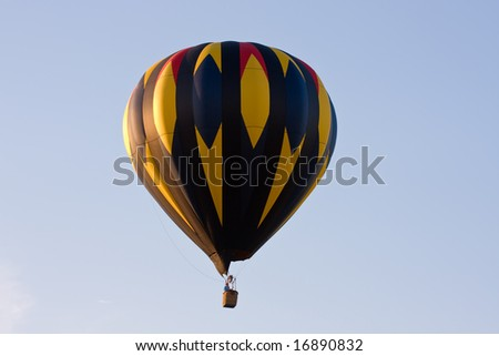 A colorful hot air balloon at a festival is suspended in mid-air on a clear day.