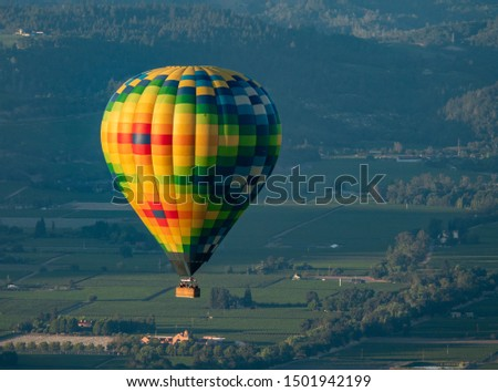 A colorful hot air balloon flies high in the sky early in the morning at sunrise above the Napa Valley, California, known for its vineyards and wineries in addition to ballooning.   #1501942199