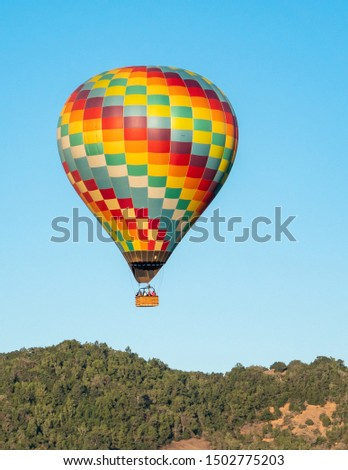 A colorful hot air balloon flies high in the sky early in the morning at sunrise above the Napa Valley, California, known for its vineyards and wineries in addition to ballooning.   #1502775203