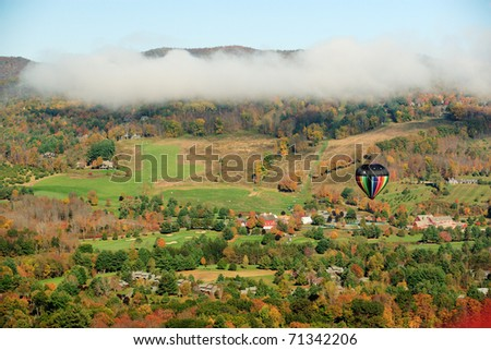 A colorful hot air balloon floating over fall foliage