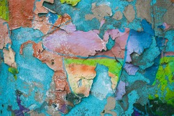 A colorful multi-colored painted grunge wall with rough plaster peels off and cracks. Blue predominates, there is also orange, green and purple colors.