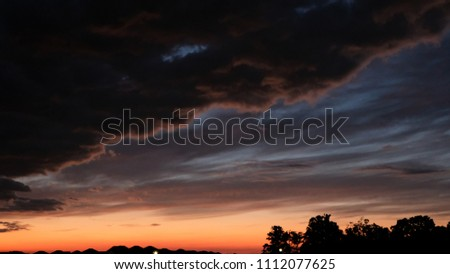 A Colorful Night Sky with Rain Clouds and Stormy Weather Approaching. Trees and Houses Line the Ground.