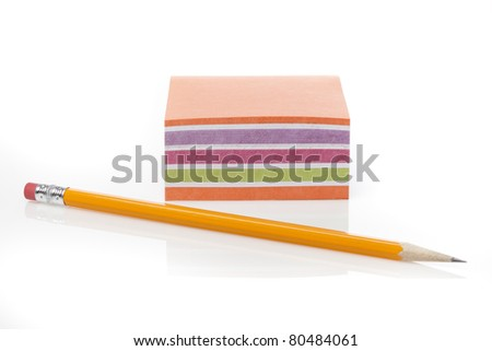 A colorful note pad with a pencil against a white background