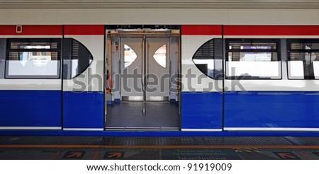 A colorful opened sliding mechanical door of a Bangkok Skytrain at a BTS train station waiting for passenger. - stock photo
