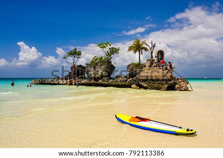 Photo of  A colorful paddle boat on Boracay beach and the Christian Shrine in the background with a beautiful sky. Boracay, Phillippines.