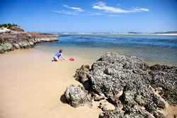 A colorful photograph of a beach in Australia with a rocky foreground, golden sand, blue sunny skies, and clear green blue water, showing a young girl with a fishing net playing at the water's edge.