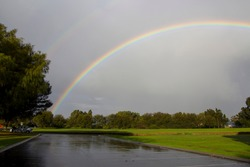 A colorful rainbow over the Big Swamp Bunbury Western Australia  on a late overcast rainy afternoon in late winter adds brilliance to the dull landscape.