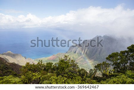 A colorful rainbow reaches across the bay with cliffs, bluffs and the Pacific Ocean below on the island of Kauai, Hawaii, USA.