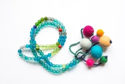 A colorful rosary with plastic beads and handcrafted decorations. isolated white background