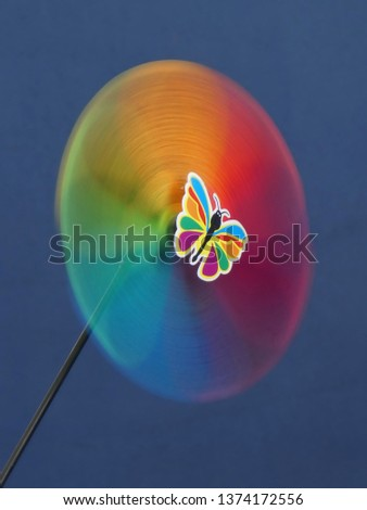 A colorful rotating toy pinwheel with a head of butterfly #1374172556