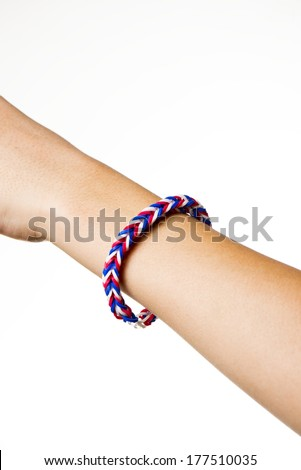 a colorful rubber band bracelet on a child's arm.