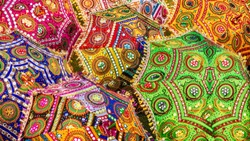 A colorful set of parasols with vibrant colors and intricate patterns, for sale as tourist souvenirs on a street in Jaipur, India.