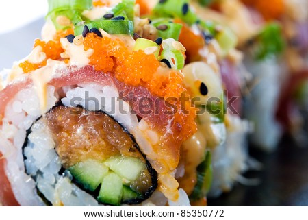 A colorful spicy Ahi tuna roll with raw seafood, fish eggs, avocado, rice and more.  Delicious Asian cuisine.