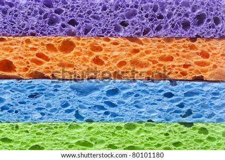 A colorful sponge used for cleaning against a white background