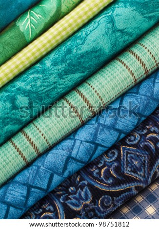 A Colorful Stack of Cloth Fabrics Set at a Diagonal Angle in Soothing Blue and Green Tones and may be Used  in a Quilt