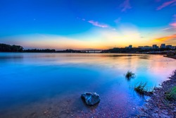 A colorful stone on the shore of a calm smooth river with a long exposure, a coast of small pebbles, after sunset, the sky is blue with a yellow sheen at dusk. White river, Ufa, Bashkortostan, Russia.