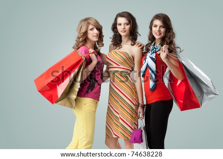 a colorful studio image of three beautiful young women standing, holding shopping bags and looking happy, smiling
