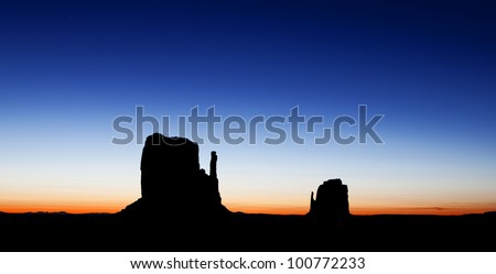 A colorful sunrise silhouette photograph of the East and West Mitten Buttes in the Monument Valley region of the Colorado Plateau that spans the northern border of Arizona and southern border of Utah.