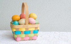 a colorful wicker Easter basket filled with speckled eggs on a lace table cloth with copy space