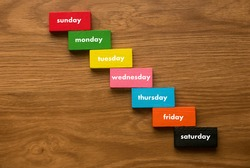 A colorful wooden block in stair shape with text of days of the week on wooden background.