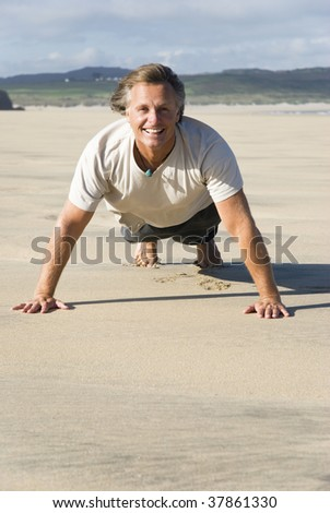 A colour photo of a happy smiling forties man performing exercises on a beautiful big sandy beach.