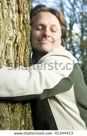 A colour portrait photo of a happy smiling forties man hugging a tree in the forest.He is a green type who cares about nature and the enviroment.