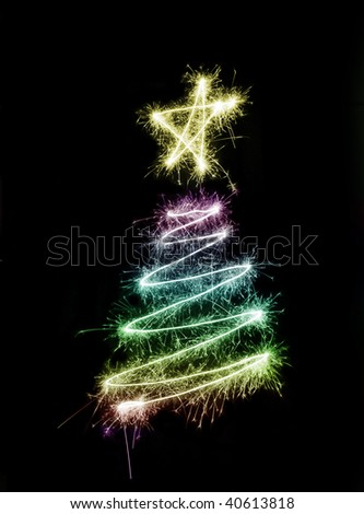 A colourful christmas tree symbol drawn in sparkler trails - stock photo