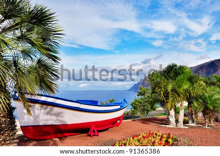 A colourful painted fishing boat on display near the ocean in Los Gigantes, Tenerife, Canary Islands, a picture postcard scenic view of the island.
