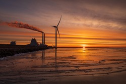 A colourful sunrise at Oresund with a powerplant and a modern Windmill close to the shore. The water is covered with ice reflecting the colours.
