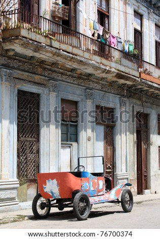A colourful tattered open top 1912 vintage car in a street of Havana, Cuba.