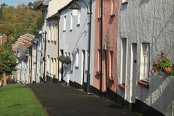 A colourful terrace of cottages sloping downhill in Bradninch, Devon