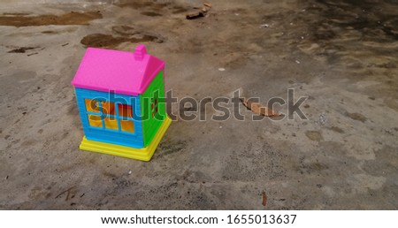 a colourful toy house on cement surface.
