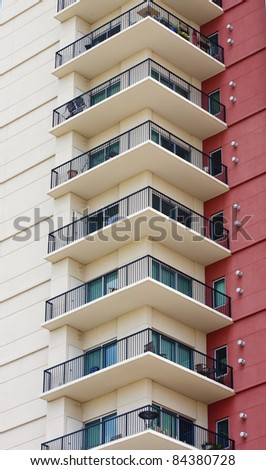 A column of condominium balconies next to a red stucco wall