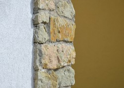 a combination of modern structural plaster and preservation of parts of the old sandstone stone wall. stone strip of yellow stones and white orange wall of the house