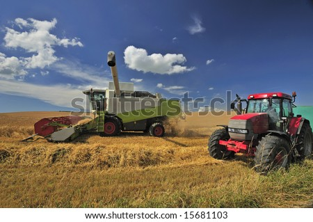 A combine harvester harvests wheat under a British summer sky. Space for text in the sky.
