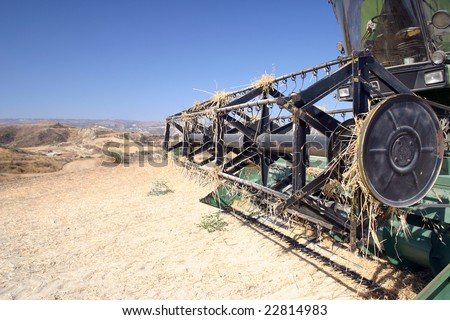 A combine harvester lies idle on land laid barren by drought