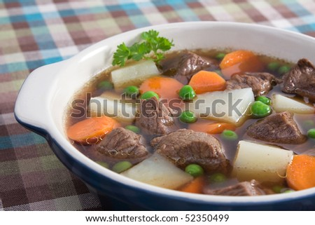 A comforting bowl of soup with beef, potatoes, carrots, and peas.