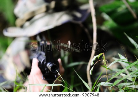 A commando aiming his weapon in the bushes