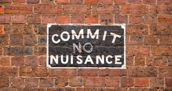 A 'Commit No Nuisance' street sign painted onto a brick wall in a city back alleyway
