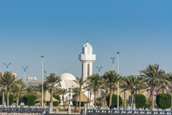 A common small mosque, Al Essa and Al Dowayan Mosque, with palm tree in the corniche coastal park in Dammam, Kingdom of Saudi Arabia