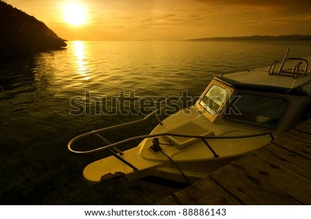 A common speedboat illuminated with sunset light. Picture taken in Raja Ampat island, papua, indonesia.  One of the most beautiful Island and diving site on earth