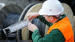 A communications engineer works with an optical fiber cable.