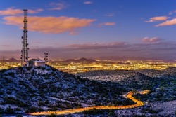 A communications tower atop Mount Suppoa looks down on the Phoenix metropolitan area. On the road below, a car's headlights streak due to the long exposure. Shot from Gila Valley Lookout after sunset.