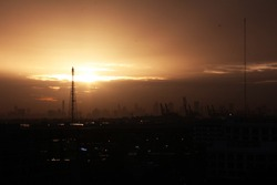 A communications tower with Sunset and pollution Covering Bangkok , A communications tower for television  and mobile phone signals.Bangchak,Thailand.Landscapes,City view.