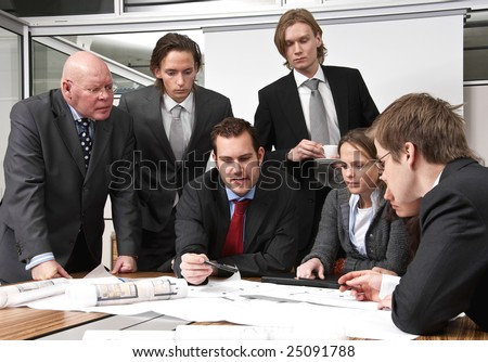 A company director and his staff, discussing plans, in a modern office cubicle